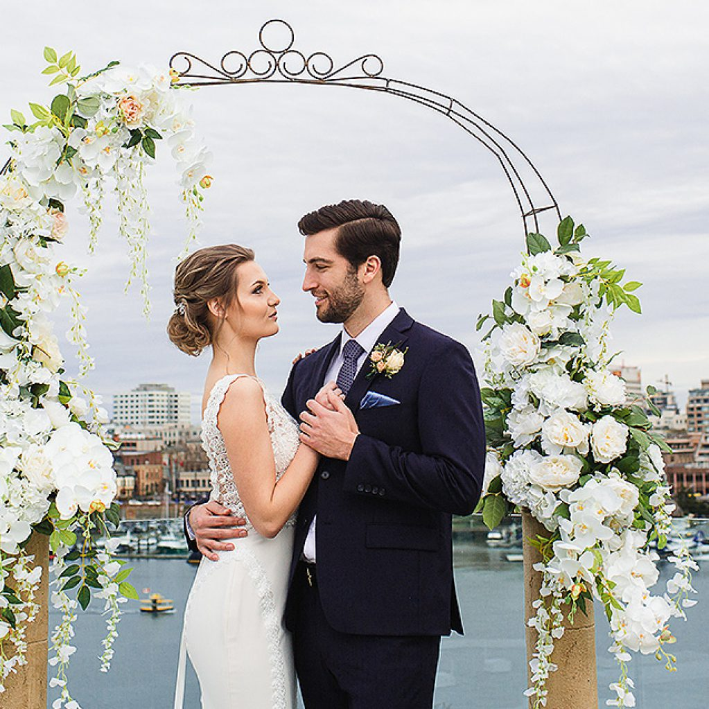Couple with flowers and scenic inner harbour in background