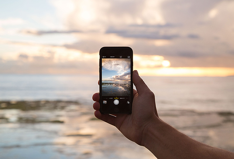 Person taking photo of sunset with phone