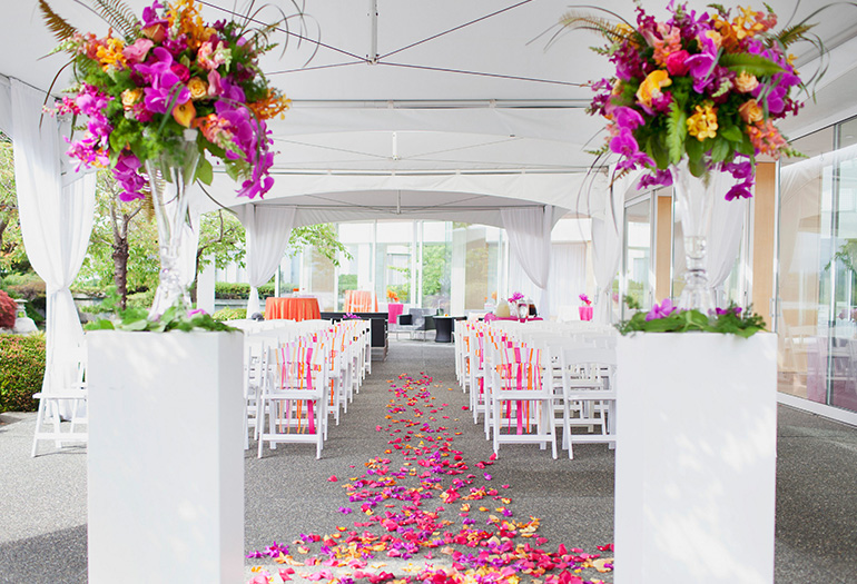 Beautiful flowers and petals decorating a pure white wedding tent