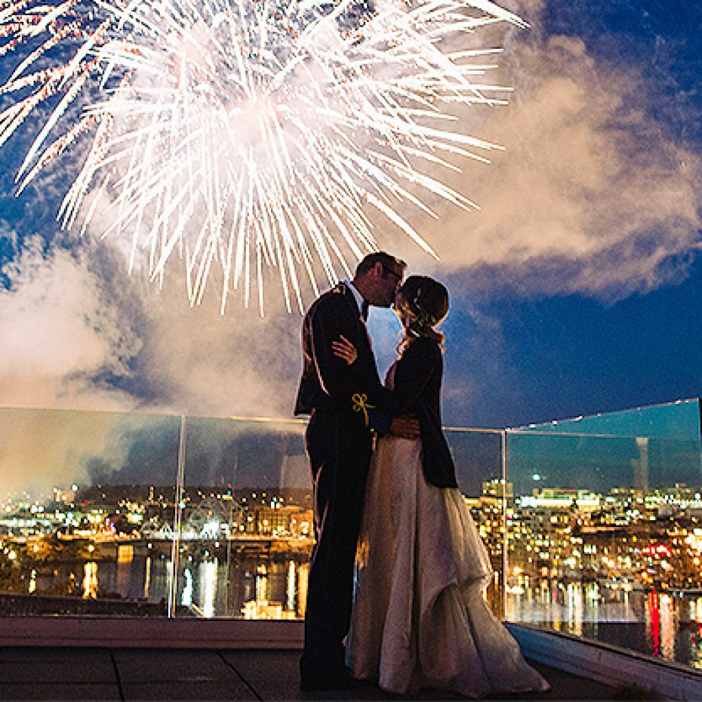Couple kissing with city and fireworks in background
