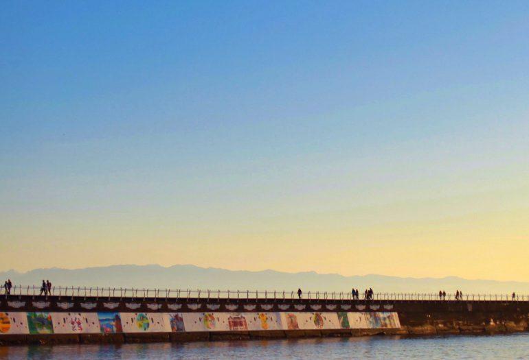 People walking along breakwater with sun setting