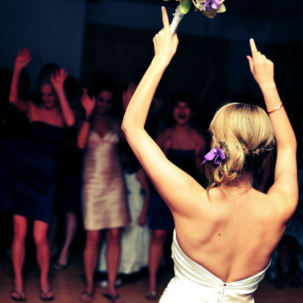 Bride tossing bouquet at wedding reception