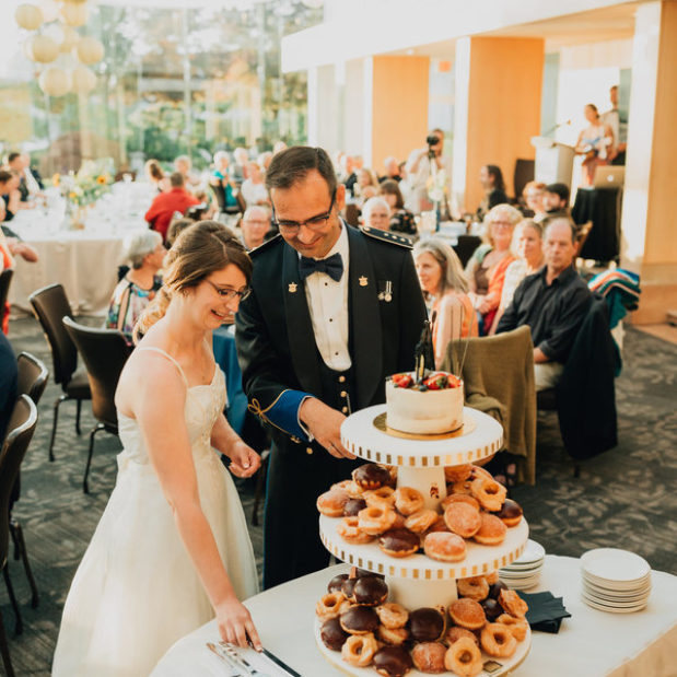 Bride and groom cutting wedding cake and donut tower