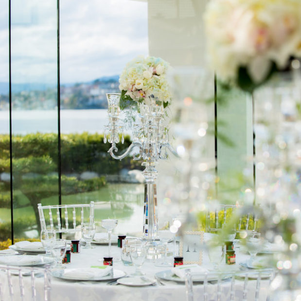 Wedding reception decor with flowers and clear chiavari chairs