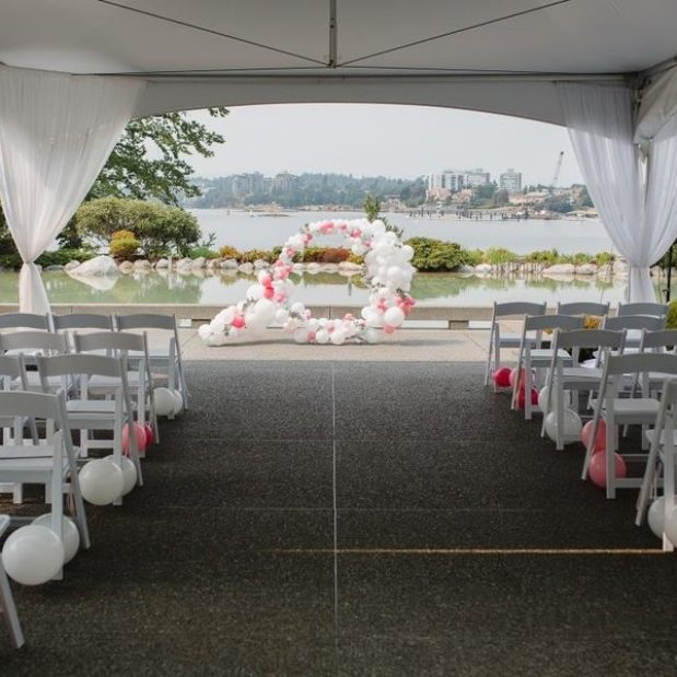 Outdoor waterfront wedding ceremony with balloon arch