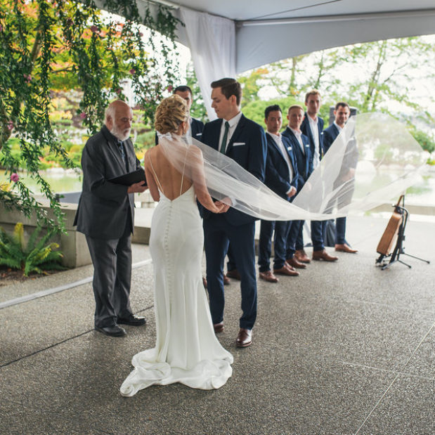 Outdoor waterfront wedding ceremony under tents