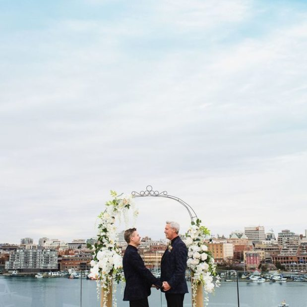 Outdoor penthouse wedding ceremony with grooms and floral arch