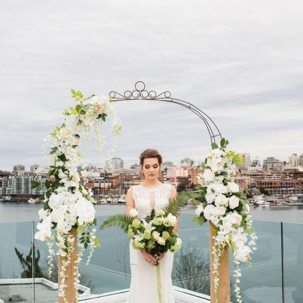 Bride portrait under floral arch with bouqet