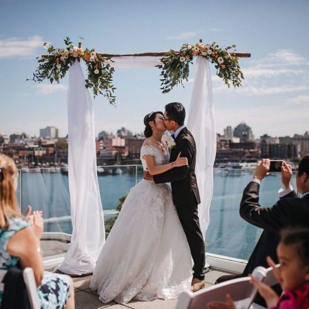 Bride and groom kissing, small outdoor penthouse wedding