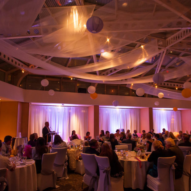 Wedding reception with paper lanterns, purple uplights