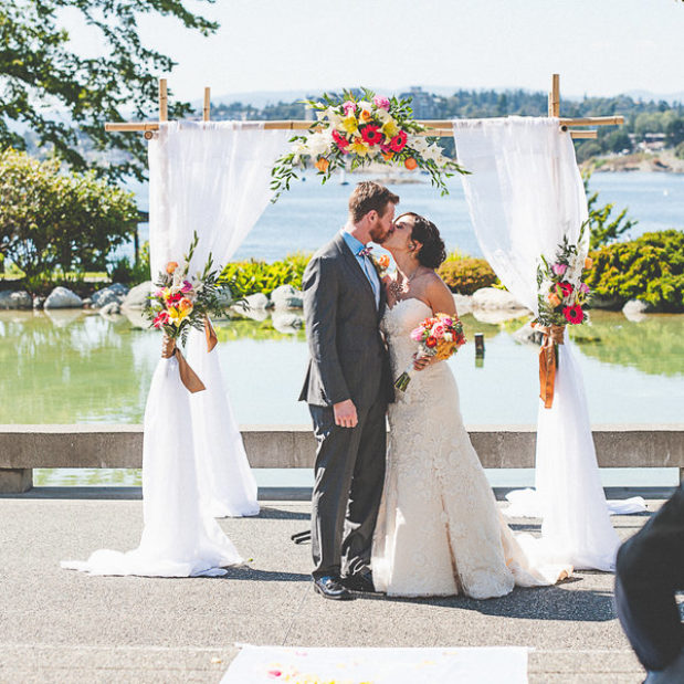 Bride and groom kissing under floral arch overlooking outer harbour