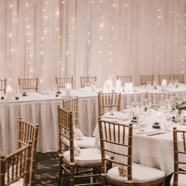 Wedding reception with head table, pipe and drape, and twinkle lights