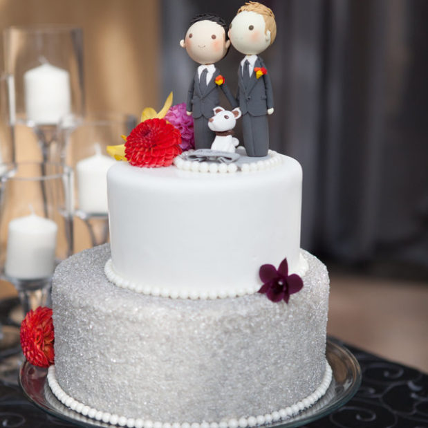 White and silver wedding cake with groom topper