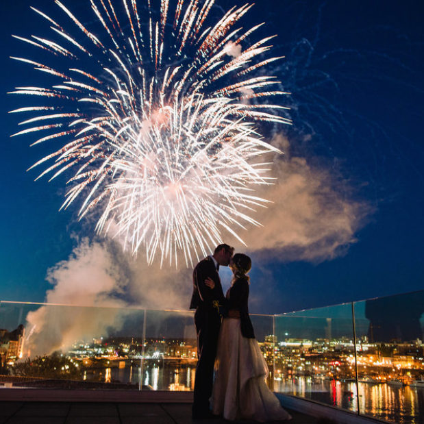 Bride and groom kissing under fireworks