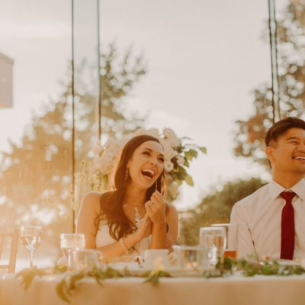 Bride and groom laughing at wedding reception