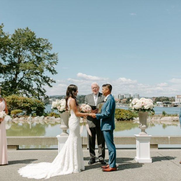 Waterfront wedding ceremony in Victoria with white pillars and florals
