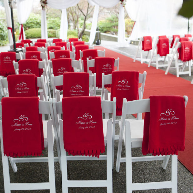 Outdoor winter wedding ceremony with red decor and blankets