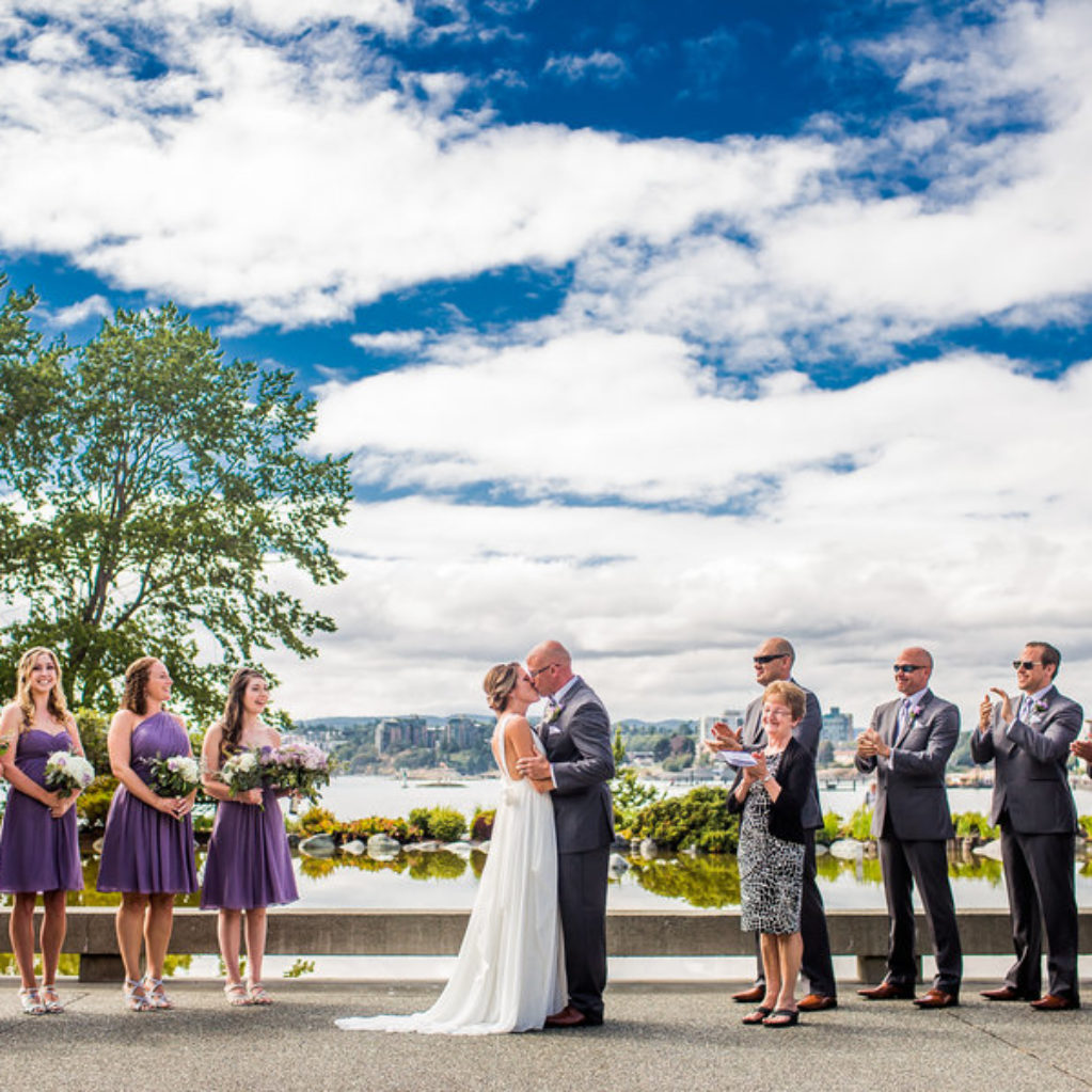 Bride and groom kissing at waterfront wedding ceremony, Victoria BC