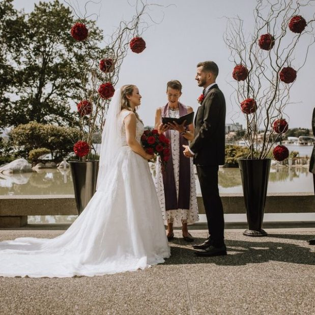 Waterfront wedding ceremony with red floral display