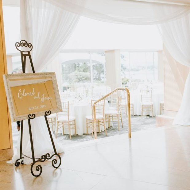 Welcome sign and entry to white themed wedding reception