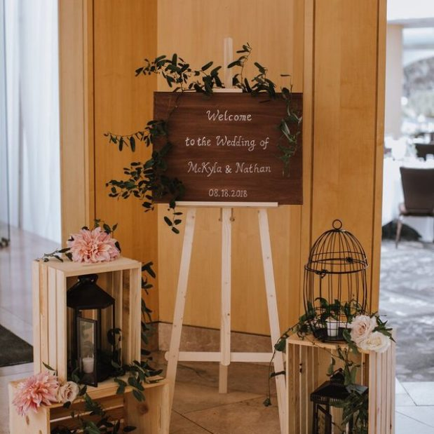 Wedding welcome sign with bird cages, lanterns, and flowers