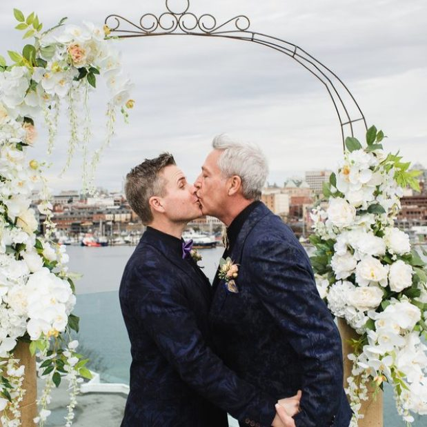 Grooms kissing under floral arch