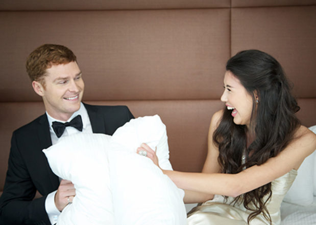 man and woman on bed laughingwith pillows between them