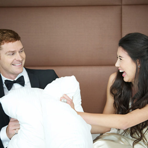 man and woman on bed laughing with pillows between them