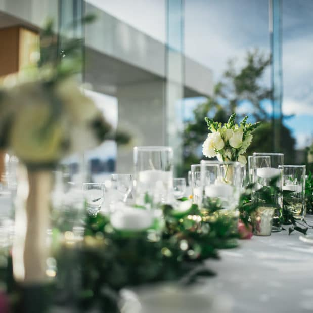 Wedding reception centrepieces with greenery and candles