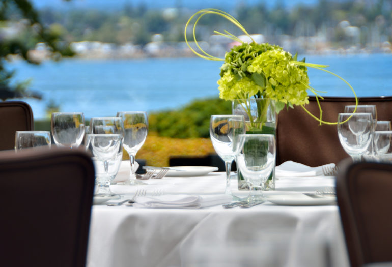 Table in Terrace Blarrom set for dinner, views of the garden and Victoria's outer harbour