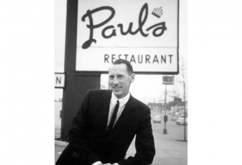 Paul Arsens standing by Paul's Restaurant Sign