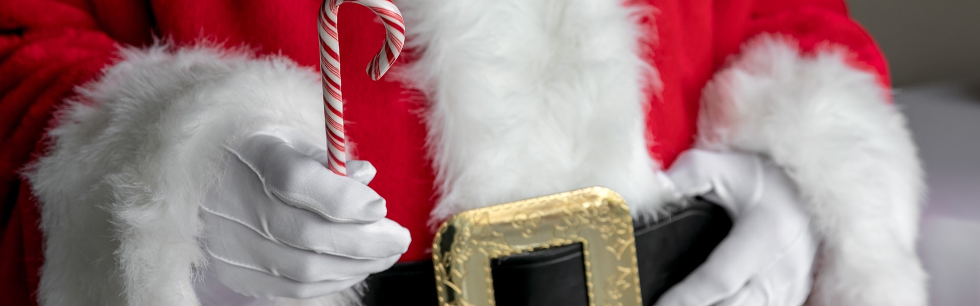 Santa Claus holding a candy cane Inn at Laurel Point Santa Claus Brunch