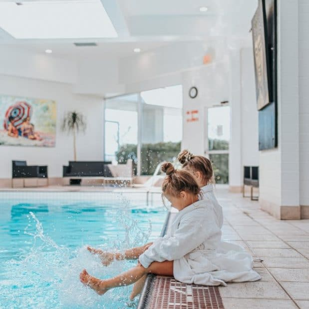 Girls sitting on pool edge in robes in Hotel Bed Inn at Laurel Point